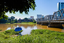 Ping River Has An Old Iron Bridge Across It. There Are Tall Buildings And Ancient Houses Next Door. In The North Of Thailand ,Chaing Mai