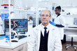 Senior male chemist looking at camera wearing protective glasses. Elderly scientist wearing lab coat working to develop a new medical vacine with african assistant in the background.