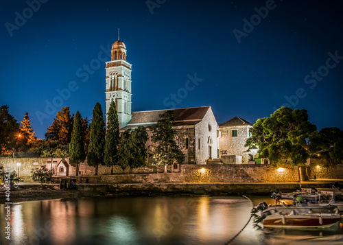 Church with a tower near the entrance to the cemetery at night on the island of Fototapet