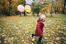 Girl Running Through The Park In The Fall With Balloons