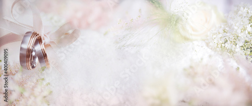 Fotografering A couple of wedding rings on blurred delicate pink background