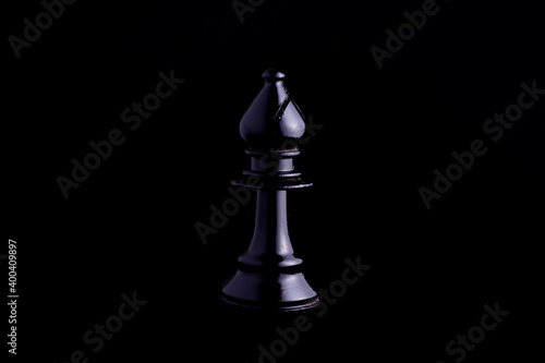 Foto one side light on Black bishop chess piece in black background
