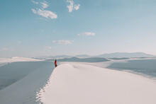A Girl In A Long Flowing Red Skirt Walking The White Gypsum Sand Dunes Of White Sands National Park, New Mexico, USA