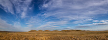 Prairie Landscape With Autumn Colored Grass And Rolling Hills With A Vivid Blue Sky And Wispy White Clouds.