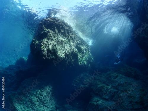Fototapety, obrazy: free diver  underwater sun beams and sun rays freediver apnea man exploring underwater rocks