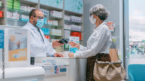 Photographie Pharmacy Drugstore Checkout Cashier Counter: Latin Pharmacist and Senior Woman Using Contactless Payment Credit Card to Buy Prescription Medicine, Vitamins