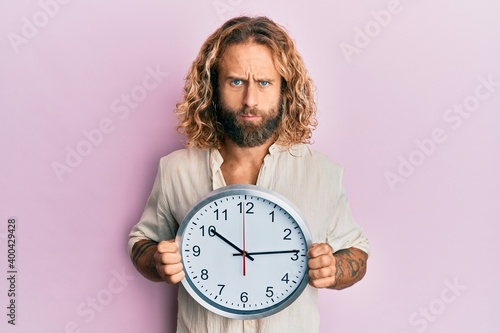 Fototapeta Handsome man with beard and long hair holding big clock skeptic and nervous, frowning upset because of problem