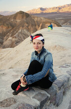 Lifestyle Photo Of Young Woman Or Girl In Jeans Jacket And Bandana With USA Flag, Sitting At Zabrisski Point In Nevada. Solo Travels During Coronavirus Covid-19 Pandemic.