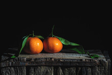 Two Orange Tangerines With Leaves On An Old Wooden Box.