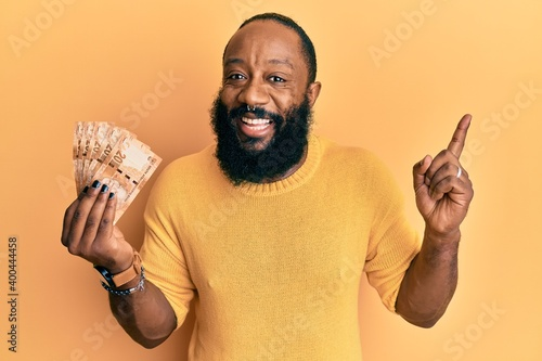 Fototapety, obrazy: Young african american man holding south african 20 rand banknotes smiling happy pointing with hand and finger to the side