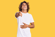 Young Hispanic Man Wearing Casual White Tshirt Laughing At You, Pointing Finger To The Camera With Hand Over Body, Shame Expression