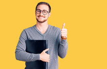 Young Handsome Caucasian Man Holding Business Folder Smiling Happy And Positive, Thumb Up Doing Excellent And Approval Sign
