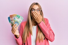 Young Blonde Woman Wearing Business Style Holding Australian Dollars Covering Mouth With Hand, Shocked And Afraid For Mistake. Surprised Expression