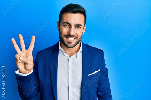 Valokuva Young hispanic businessman wearing business jacket showing and pointing up with fingers number three while smiling confident and happy