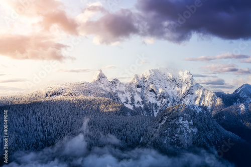 Beautiful aerial landscape view of Mountain Peaks near Vancouver, British Columbia, Canada. Dramatic Stormy Cloudy Sunset Sky Art Render.