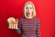 Young Blonde Woman Eating Fried Chicken Scared And Amazed With Open Mouth For Surprise, Disbelief Face