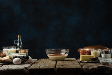 The Glass Bowl With A Dough. Backstage Of Cooking Waffle On Rustic Wooden Table With Ingredients On Dark Blue Background. Frozen Motion. Handmade Dessert. Cooking Process.