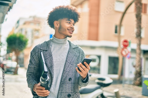 Fotografie, Tablou Young african american businessman using smartphone holding bottle of water at the city