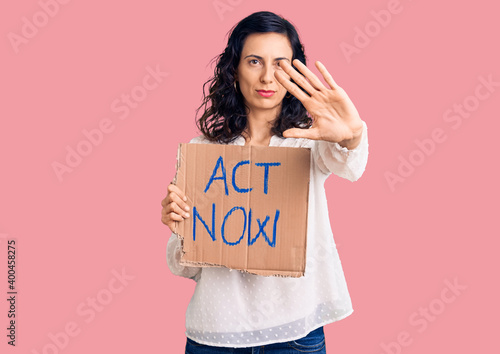 Fototapeta Young beautiful hispanic woman holding act now banner with open hand doing stop sign with serious and confident expression, defense gesture obraz