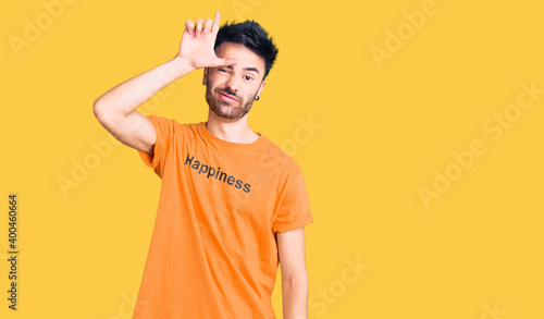 Young hispanic man wearing t shirt with happiness word message making fun of people with fingers on forehead doing loser gesture mocking and insulting Fototapet