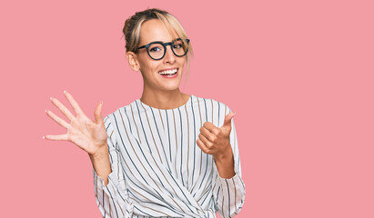 Beautiful blonde woman wearing business shirt and glasses showing and pointing up with fingers number six while smiling confident and happy.
