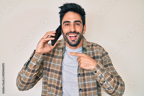 Handsome hispanic man with beard having conversation talking on the smartphone smiling and laughing hard out loud because funny crazy joke. - fototapety na wymiar