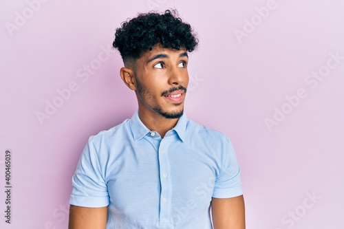 Photo Young arab handsome man wearing casual clothes looking to side, relax profile pose with natural face and confident smile