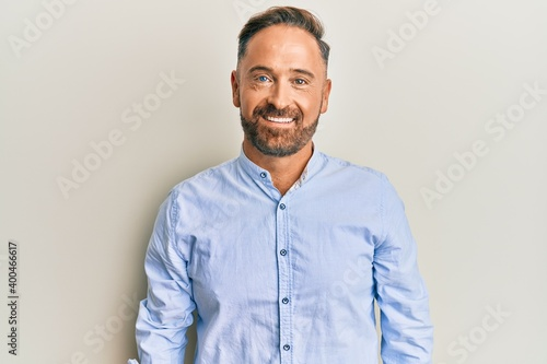 Obraz Handsome middle age man wearing business clothes with a happy and cool smile on face. lucky person. - fototapety do salonu