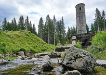 Old Stone Tower Above A Stream With Boulders At A Place Of A Broken Dam