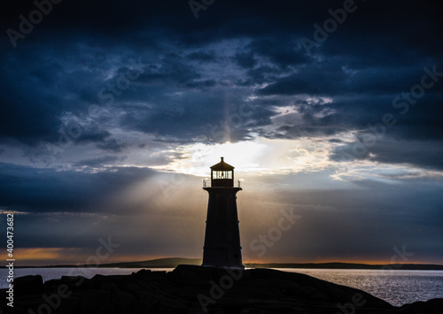Peggy's Cove lighthouse at sunset with storm clouds Fototapeta