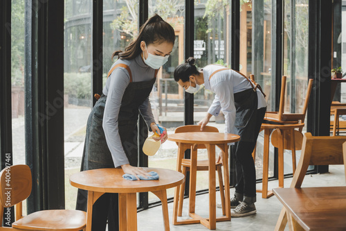Billede på lærred asian waitress staff wearing protection face mask in apron cleaning table with disinfectant spray for protect infection coronavirus (covid-19) in cafe coffee shop restaurant