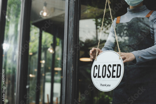 Fototapeta small business owner woman wearing protection face mask turning closed sign board on glass door for open cafe restaurant after coronavirus (covid-19) quarantine. reopen shop, food and drink concept obraz