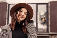 Close Up Shot Charming Woman Standing Outside Near Street Cafe Restaurant Wear Brown Hat Gray Coat Poloneck Black Sweater, Looking At The Camera. Girl Spend Time Autumn Spring, Cold Weather Fresh Air