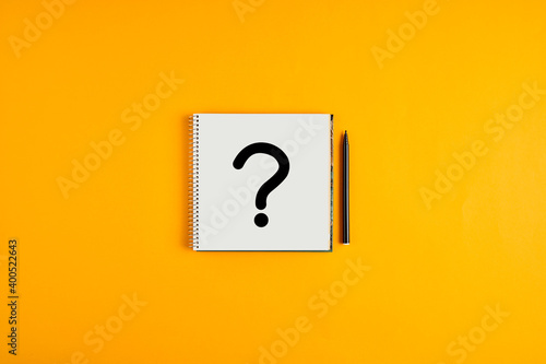 Fototapeta Question mark drawn on a notepad with black pen next to it against yellow background obraz