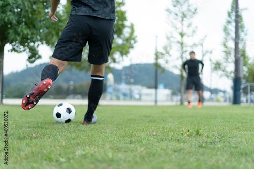 Fotografiet 公園でサッカーをする若い男性