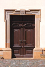 Brown Wooden Door In A Baroque Sandstone Portal With An Old Keystone On The Facade Of The Rehborn Village Church In Germany