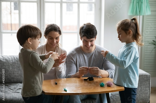Obraz Happy family with two kids sculpting from plasticine at home, sitting on couch, smiling mother and father with adorable little daughter and son involved in creative activity, enjoying leisure time - fototapety do salonu