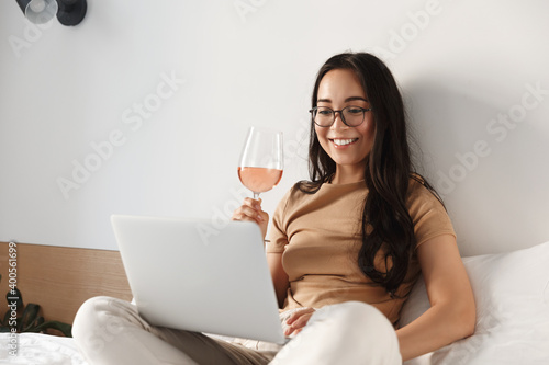 Photo Image of young happy asian woman having video call, sitting on bed and drinking
