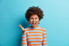 Beautiful Dark Skinned Woman With Curly Hair Raises Hand And Shouts Loudly Stands Mad Irritated Expresses Anger Rage Wears Striped Casual Jumper Isolated Over Blue Background. Negative Emotions