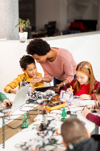 Fototapeta African American female science teacher with group of kids programming electric