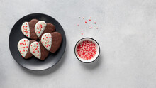 Valentine Heart Cookies With White Chocolate And Colorful Sprinkles On Dark Plate. Valentines Day Concept. Gray Background. Top View. Banner. Copy Space
