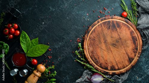 Fototapeta culinary background with spices, herbs and kitchen utensils. Top view. Rustic style. obraz