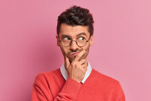 Handsome Thoughtful Man Holds Chin And Looks Doubtful Away Purses Lips Makes Planning Tries To Decide What To Do Better Has Stylish Hairdo Wears Transparent Round Glasses Poses Indoor Over Rosy Wall