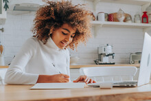 Student Girl With Trendy Kinky Hair Sitting Against Notebook And Writing Notes In Copybook Enjoying Online Education Closeup