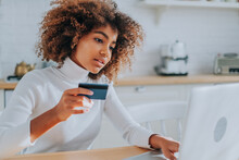 Lady With Perfect Dark Skin Holding Credit Card And Inserting Bank Information For Online Shopping Sits Near Laptop Closeup