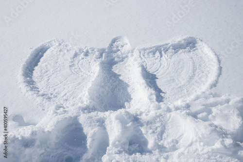 Fotografia snow angel drawing on covered field, childrens activity in winter