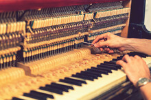 Piano Tuning Process. Closeup Of Hand And Tools Of Tuner Working On Grand Piano. Detailed View Of Upright Piano During A Tuning. Toned