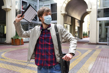 An Office Worker Wearing A Medical Mask Who Has Been Fired From His Job Strikes Outside An Office Building. Concept Of Unemployment And Layoffs, Economic Crisis