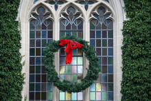 Pine Wreath With Red Ribbon On Exterior Of Gothic Stone Framed Leaded Glass Church Window