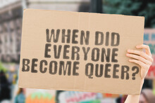 "The Question "" When Did Everyone Become Queer ? "" On A Banner In Men's Hand With Blurred Background. LGBT. Sexual Orientation. Sexuality. Homosexuality. Relationship. Human Rights. Equality"